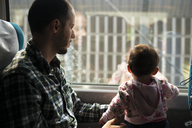 Father and baby girl traveling by train looking out of window - GEMF01870