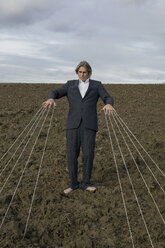 Businessman standing on a field tied to strings - PSTF00063