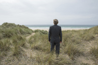 UK, Cornwall, Hayle, businessman standing in beach dunes looking at view - PSTF00078