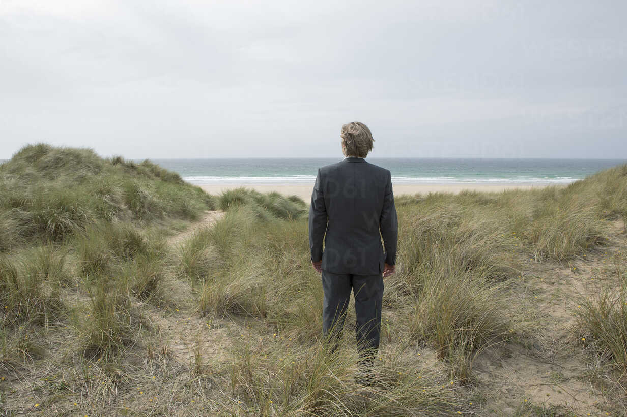 UK, Cornwall, Hayle, businessman standing in beach dunes looking at view - PSTF00078 - Petra Stockhausen/Westend61