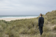 UK, Cornwall, Hayle, businessman standing in beach dunes looking at view - PSTF00081
