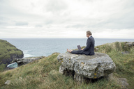 UK, Cornwall, Tintagel, businessman sitting on rock at the coast using laptop - PSTF00084