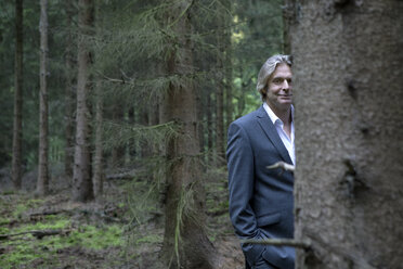 Portrait of smiling businessman in forest - PSTF00087