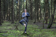 Businessman practicing yoga in forest - PSTF00090