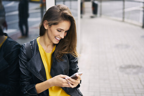 Happy woman looking at cell phone - BSZF00202