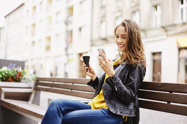 Portrait of happy woman sitting on bench with ice cream cone looking at  cell phone - BSZF00205
