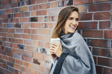Portrair of young woman with coffee to go in front of brick wall - BSZF00208