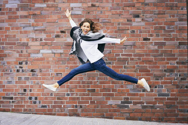 Happy young woman jumping in the air in front of brick wall - BSZF00211
