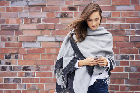 Smiling young woman looking at cell phone in front of brick wall - BSZF00214