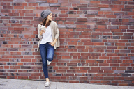 Young woman with coffee to go leaning at brick wall - BSZF00220