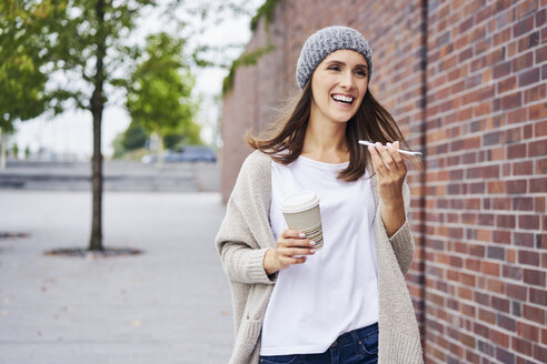 Portrait of happy woman with coffee to go on the phone - BSZF00223