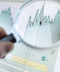 Investor analysing line graph on computer screen with magnifying glass - ABRF00072