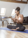 Young woman sitting on yoga mat using cell phone - MADF01372