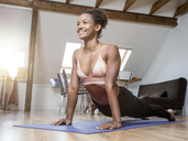Smiling young woman practicing yoga - MADF01378