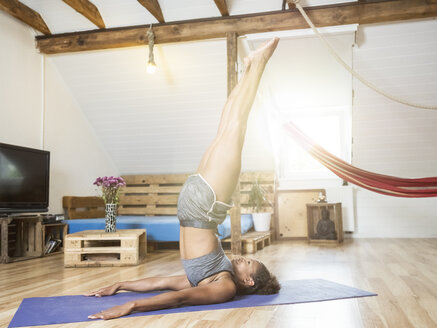 Young woman practicing yoga in attic - MADF01381