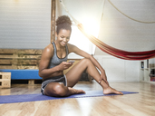 Smiling young woman sitting on yoga mat looking at cell phone - MADF01384