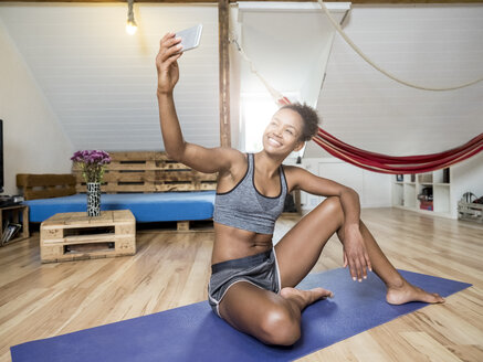 Smiling young woman sitting on yoga mat taking a selfie - MADF01387