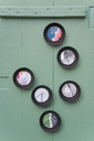 Photos in upcycled baking dishes hanging on a green wooden wall - GISF00303