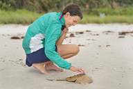 USA, Florida, Naples, barefoot girl touching carcass of a horseshoe crab on the beach - SHF01993