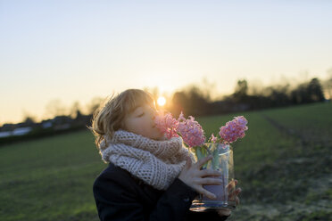 Boy on a meadow smelling hyacinth at sunset - KMKF00153