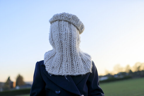 Boy covering his face with knitted round scarf - KMKF00156
