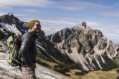 Austria, Tyrol, smiling young man on a hiking trip in the mountains - UUF12553