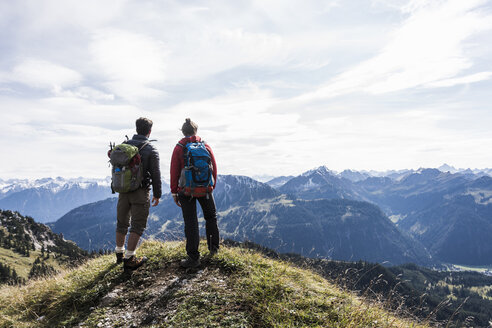 Austria, Tyrol, young couple standing in mountainscape looking at view - UUF12562