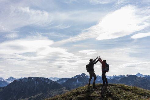 Austria, Tyrol, young couple standing in mountainscape cheering - UUF12565