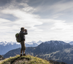 Austria, Tyrol, young man standing in mountainscape looking at view with binoculars - UUF12574
