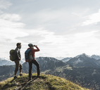 Austria, Tyrol, young couple standing in mountainscape looking at view - UUF12577