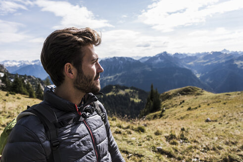 Austria, Tyrol, portrait of young man in mountainscape looking at view - UUF12580