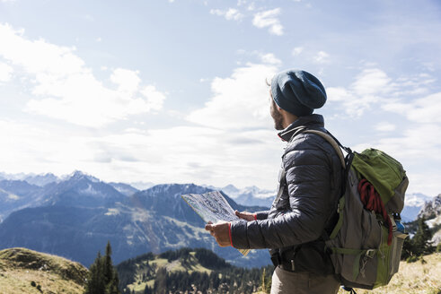 Austria, Tyrol, young man with map in mountainscape - UUF12583