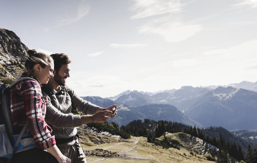 Austria, Tyrol, smiling young couple taking a selfie in mountainscape - UUF12595