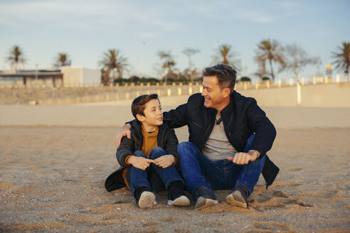 Smiling father embracing son on the beach - EBSF02018