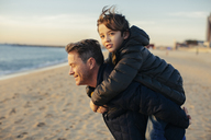 Portrait of father carrying son piggyback on the beach - EBSF02021