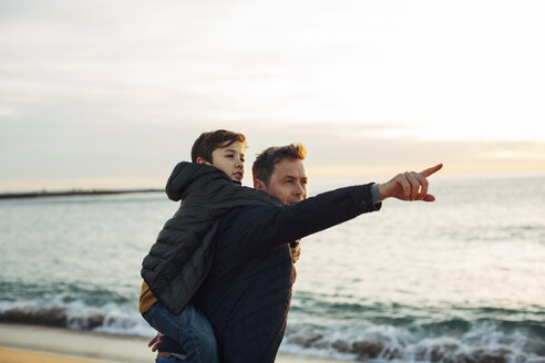 Father carrying son piggyback on the beach at sunset pointing finger - EBSF02024