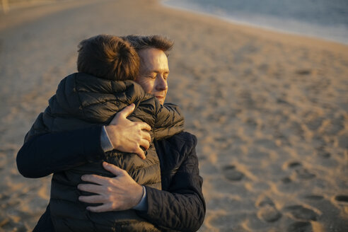 Father hugging son on the beach - EBSF02027