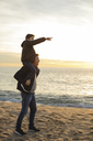 Father carrying son piggyback on the beach at sunset pointing finger - EBSF02033