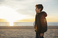 Boy holding football on the beach at sunset - EBSF02036