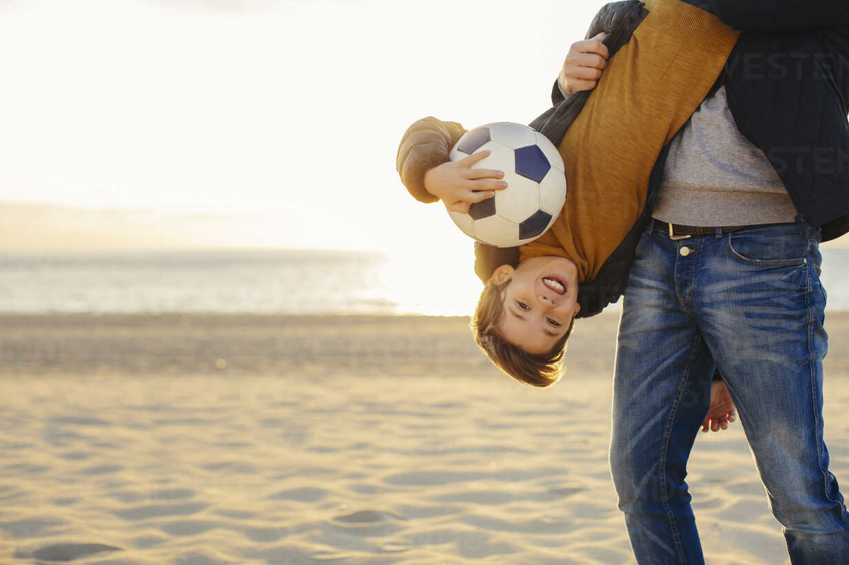 Father holding son with football upside down on the beach at sunset - EBSF02045 - Bonninstudio/Westend61