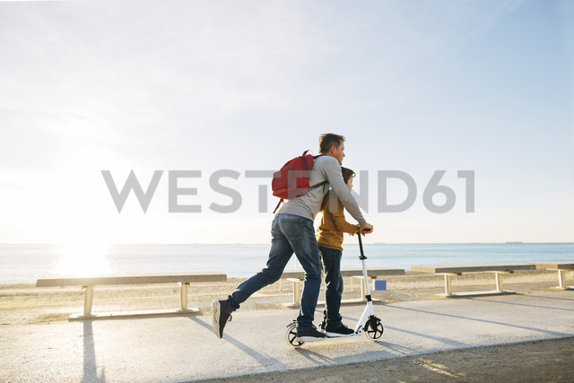 Father and son riding scooter on beach promenade at sunset - EBSF02051 - Bonninstudio/Westend61