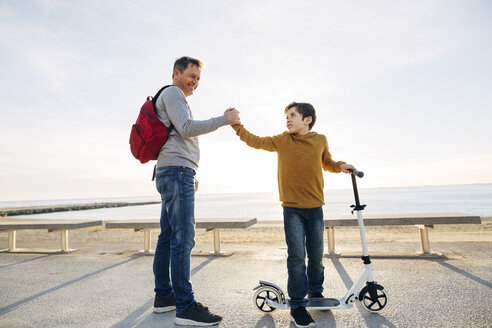 Father and son with scooter shaking hands on beach promenade at sunset - EBSF02054