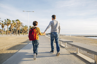 Father and son walking on beach promenade - EBSF02060