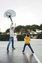 Father and son playing basketball on an outdoor court - EBSF02063