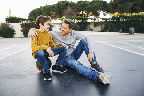 Father embracing son on basketball outdoor court - EBSF02066