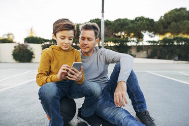 Father and son sitting on basketball outdoor court using cell phone - EBSF02069