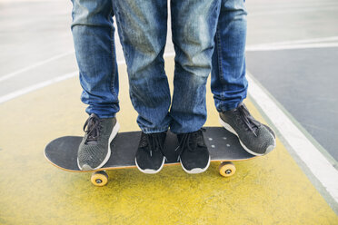 Legs of adult and child on skateboard - EBSF02072
