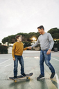Father assisting son riding skateboard - EBSF02075