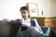 Portrait of pensive man with coffee mug and tablet sitting on couch at home - SGF02150