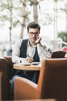 Young man working in a cafe using tablet and taking notes - UUF12599